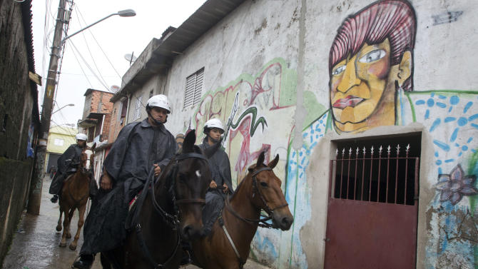 Mounted military police patrol in the Paraisopolis slum of Sao Paulo, Brazil, early Tuesday, Nov. 13, 2012. At least 140 people have been murdered in South America's biggest city over the past two weeks in a rising wave of violence, Sao Paulo's Public Safety Department said on Sunday. (AP Photo/Andre Penner)