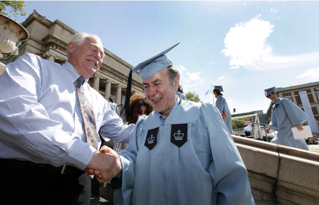 Columbia University janitor Gac Filipaj, center, is congratulated by his boss, Donald Schlosser, the assistant vice president of facility operations, during the Columbia University School of General S
