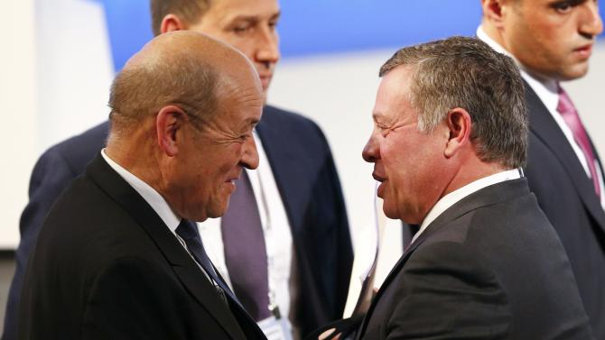Jordan's King Abdullah greets French Defence Minister Le Drian at the Munich Security Conference in Munich