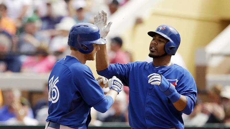 Toronto Blue Jays' Dan Johnson, left, is congratulated by Edwin Encarnacion after they both scored on Johnson's two-run home run during the seventh inning of a spring exhibition baseball game against the Detroit Tigers in Lakeland, Fla., Tuesday, March 11, 2014