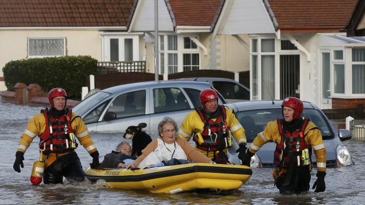 Emergency rescue service workers evacuate residents in an inflatable boat in flood water in a residential street in Rhyl