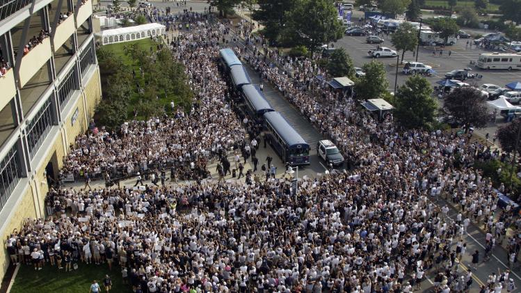 Penn State football fans surround the Penn State football team as they arrive by bus at Beaver Stadium for their season opener NCAA college football game against Ohio in State College, Pa., Saturday, Sept. 1, 2012. (AP Photo/Gene J. Puskar)