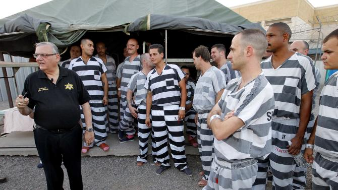 """Inmates gather next to Maricopa County Sheriff Joe Arpaio as he walks through a Maricopa County Sheriff's Office jail called """"Tent City"""" in Phoenix on Saturday, June 23, 2012 during a tour for church leaders. Critics of Arpaio gathered outside the facility Saturday for a rally to call for the closure of the complex of canvas jail tents. (AP Photo/Matt York)"""