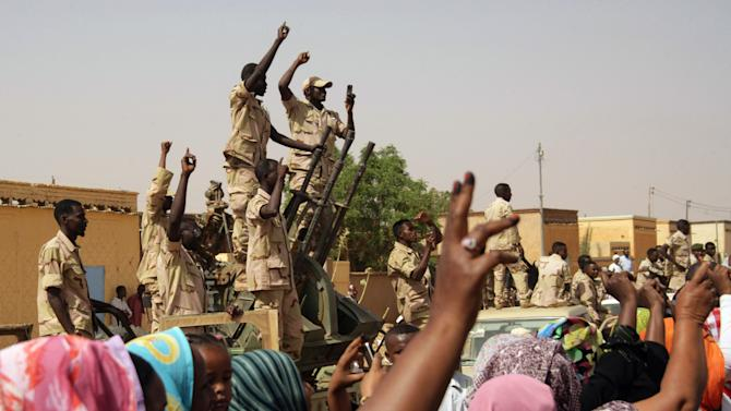 """Sudanese troops react to a visit by President Omar al-Bashir in al-Obeid, North Kordofan, Sudan, Thursday, April 19, 2012. The Arab League said Thursday it would hold an emergency meeting over the increasing violence between Sudan and South Sudan. Sudan President Omar al-Bashir on Wednesday threatened to topple the South Sudan government after accusing the south of trying to take down his Khartoum-based government. Al-Bashir continued his hardline rhetoric on Thursday in an address to a """"popular defense"""" brigade headed to the Heglig area. The ceremony was held in al-Obeid, in northern Kordofan. (AP Photo/Abd Raouf)"""