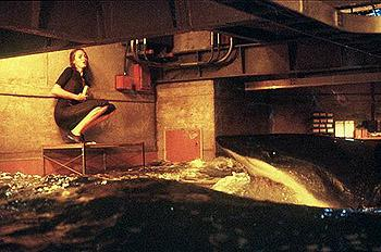 Dr. Susan McAlester ( Saffron Burrows ) cowers in fear from a deadly shark in Warner Brothers' Deep Blue Sea