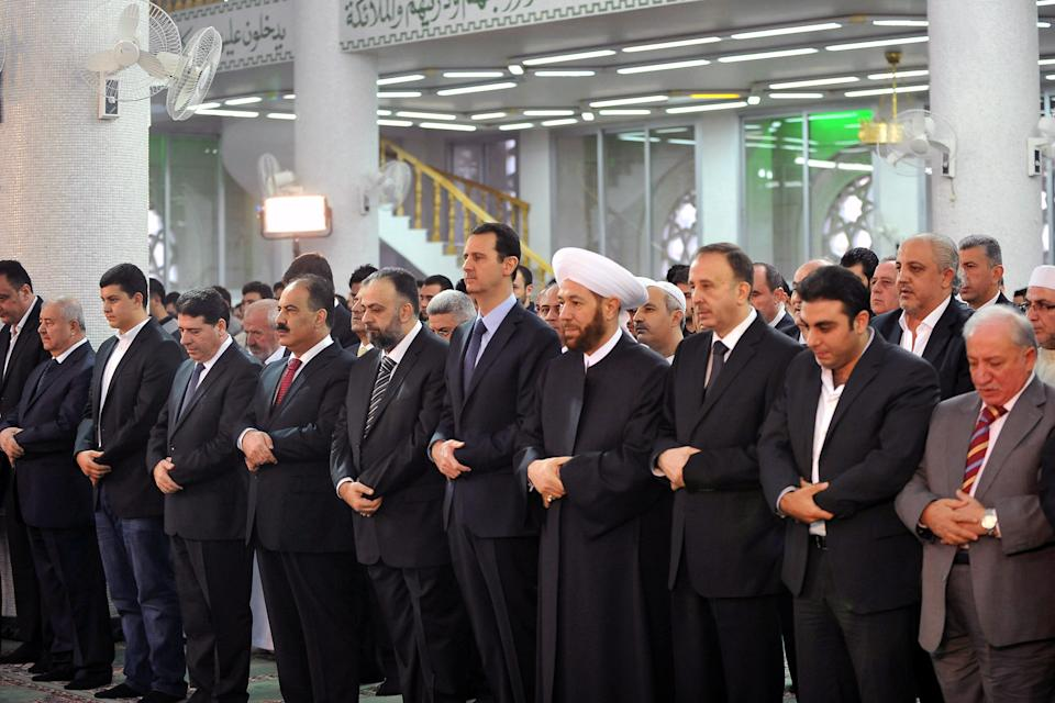 In this photo released by the Syrian official news agency SANA, Syrian President Bashar Assad, fifth from right, prays during the Eid al-Adha prayer at the Sayeda Hassiba mosque, in Damascus, Syria, Tuesday, Oct. 15, 2013. (AP Photo/SANA)