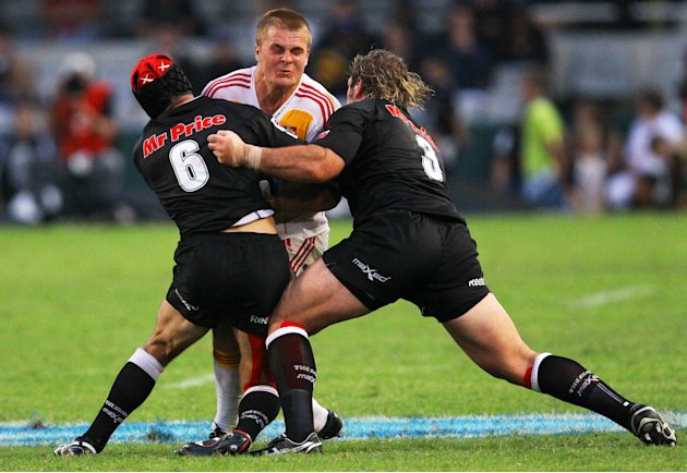 New Zealand Waikato Chiefs'  Sam Cane (C) is tackled by Durban Sharks' players during a Super 15 rugby union match at the Mr Price Kings Park Rugby Stadium on April 21, 2012.  AFP PHOTO (Photo credit