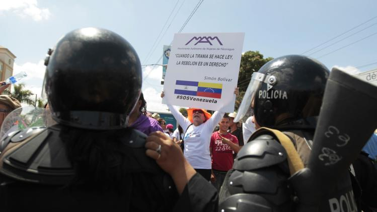 A feminist activist holds a sign during an International Women's Day march in Managua
