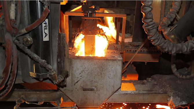 In this May 12, 2014 photo, molten metal is cast at Rochester Metal Products Corp. in Rochester, Ind. The hulking induction furnaces the plant uses to melt scrap iron consume enough electricity to power 7,000 households. (AP Photo/AJ Mast)