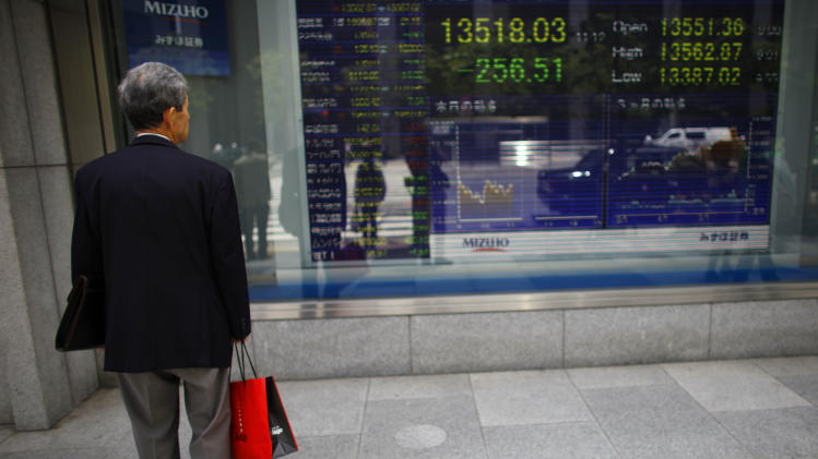 A man looks at an electronic stock board outside a securities firm Monday, June 3, 2013, in Tokyo.  Uncertainty about the U.S. Federal Reserve's next course of action and a sharp, sudden plunge on Wall Street sent Asian stock markets lower Monday. Japan's Nikkei 225 index lost 2.2 percent to 13,475.64, echoing U.S. stock markets losses Friday. The Dow dropped more than 200 points, its worst drop in six weeks.  (AP Photo/Junji Kurokawa)