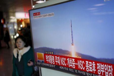 A passenger walks past a TV screen broadcasting a news report on North Korea's long range rocket launch at a railway station in Seoul