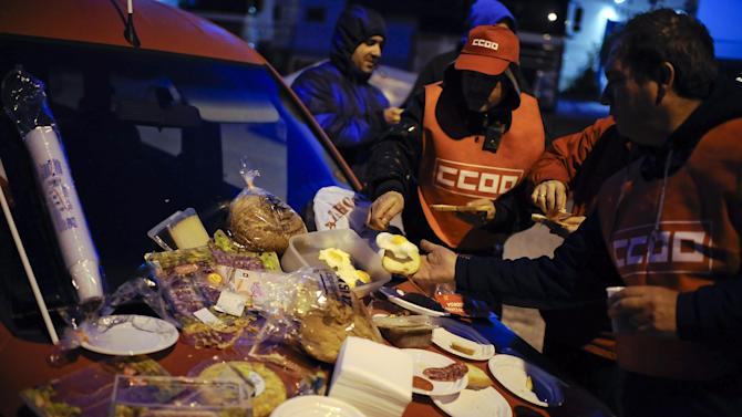 Trade Unions take a breakfast early in the morning outside of a factory during a general strike against government austerity measures, in Pamplona, northern Spain, Wednesday, Nov. 14, 2012. A  Spanish Interior Ministry official says 32 people have been arrested and 15 people treated for minor injuries in disturbances as a general strike in Spain against austerity measures and economic reforms began. The General Workers Union said the nationwide stoppage, the second this year, was being heeded by nearly 100 percent of workers Wednesday in the automobile, energy, shipbuilding and constructions industries. (AP Photo/Alvaro Barrientos)