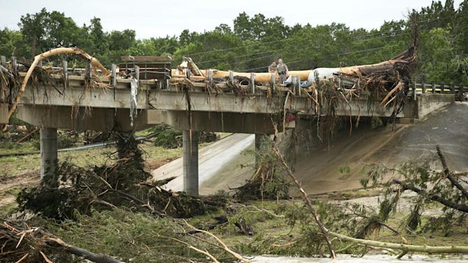 A large tree rests on the Hwy 12 bridge over the Blanco River in Wimberley, Texas, Sunday May 24, 2015. Flooding in Texas and Oklahoma has led to numerous evacuations. (Jay Janner/Austin American-Statesman via AP) AUSTIN CHRONICLE OUT, COMMUNITY IMPACT OUT, INTERNET AND TV MUST CREDIT PHOTOGRAPHER AND STATESMAN.COM, MAGS OUT