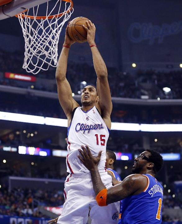 Los Angeles Clippers' Ryan Hollins, left, dunks the ball over New York Knicks' Amar'e Stoudemire during the first half of an NBA basketball game in Los Angeles, Wednesday, Nov. 27, 2013