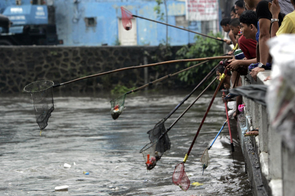Men use a pole with a net as they wait to scoop any salvagable materials from rising water Tuesday, Aug. 2, 2011 in suburban Quezon City, north of Manila, Philippines. Waist-deep floods have swamped the streets in the Philippine capital after a night of monsoon rains closed down schools and government offices. (AP Photo/Pat Roque)