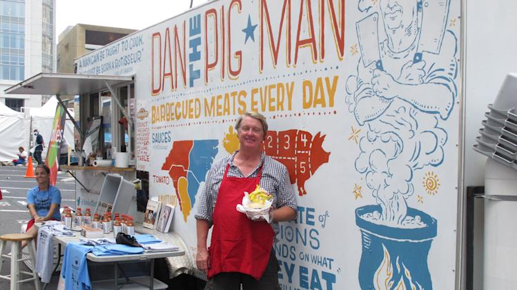 "Dan Huntley, also known as ""Dan the Pig Man"" holds up one of his barbecue sandwiches outside his food truck in Charlotte, N.C. on Tuesday, Sept. 4, 2012. Huntley had his best day ever during the convention, selling $10,000 worth of sandwiches. (AP Photo/Jeffrey Collins)"