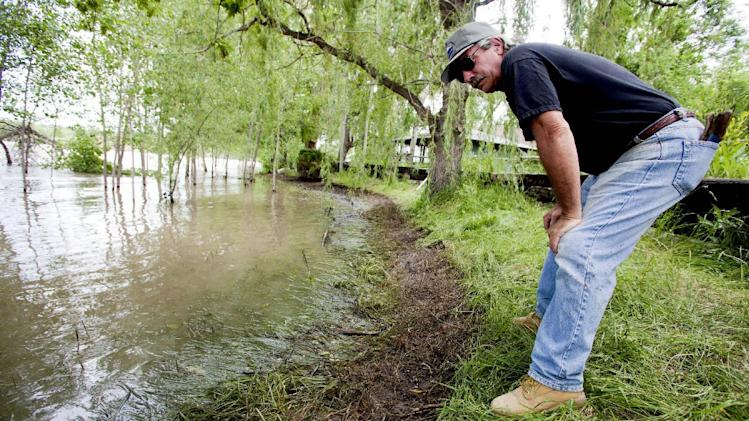 FILE - This July 4, 2011 file photo shows Jim Swanson surveying the oil impact on his property in Laurel, Mont. Swanson had contacted the DEQ after seeing oil sheens along the river. His property suffered extensive contamination last year that Exxon workers attempted to remove as part of an estimated $135 million cleanup and repair job.  (AP Photo/Jim Urquhart, File)