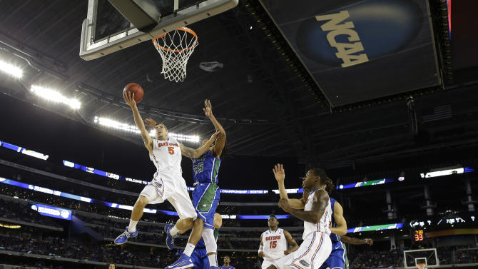 Florida's Scottie Wilbekin (5) shoots as Florida Gulf Coast's Sherwood Brown (25) defends during the second half of a regional semifinal game in the NCAA college basketball tournament, Saturday, March 30, 2013, in Arlington, Texas. (AP Photo/Tony Gutierrez)