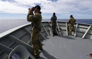Gunner Brown of Transit Security Element looks through binoculars as he stands on lookout with other crew members aboard Australian Navy ship HMAS Perth as they continue to search for missing Malaysian Airlines flight MH370