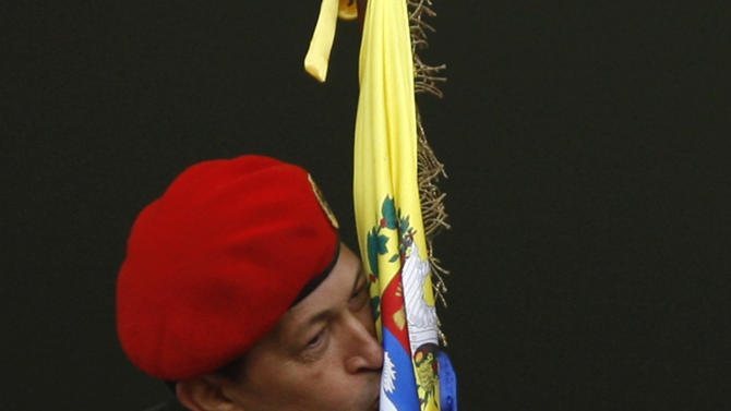 Venezuela's President Hugo Chavez kisses a Venezuelan flag after greeting supporters at a balcony of Miraflores presidential palace in Caracas, Venezuela, Monday, July 4, 2011. Chavez returned to Venezuela from Cuba on Monday morning, stepping off a plane hours before dawn and saying he is feeling better as he recovers from surgery that removed a cancerous tumor. (AP Photo/Ariana Cubillos)