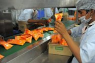Employees on an ice cream production line at the Mother Dairy factory at Bhatt village on the outskirts of Ahmedabad, northern India, on May 30. India's industrial output grew just 0.1 percent in April year-on-year, official data showed Tuesday, adding to concerns about the economy and raising the chances of an interest rate cut next week