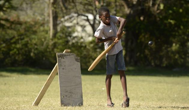 Boy plays shot during a cricket match with friends at Belleplaine