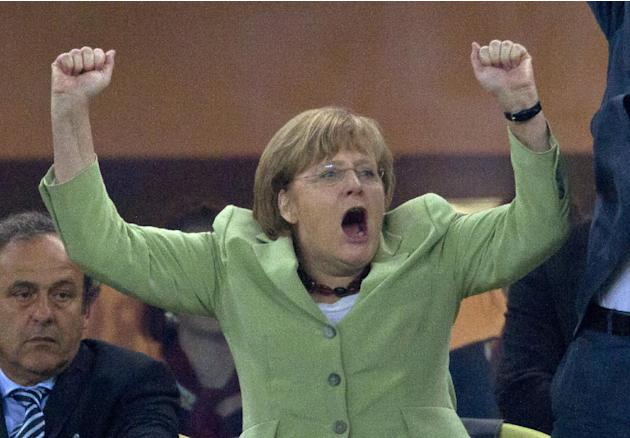 The June 22, 2012 file photo shows German Chancellor Angela Merkel celebrating during the  Euro 2012  quarterfinal soccer match between Germany and Greece in Gdansk, Poland, Friday, June 22, 2012. Ger