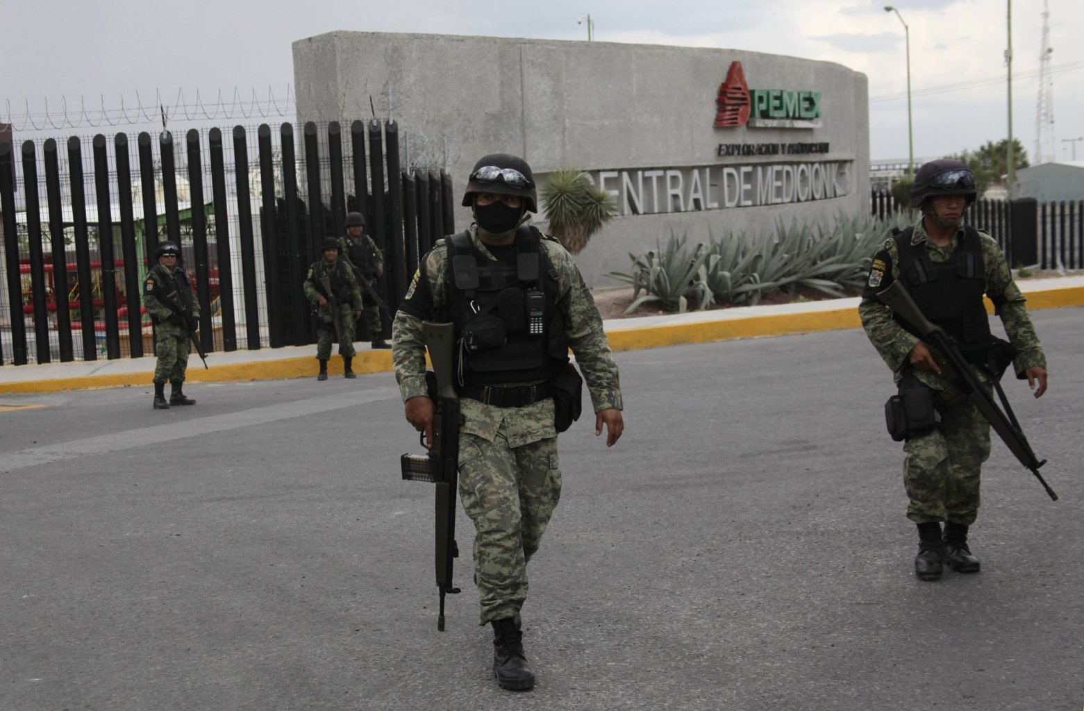 Soldiers walk outside a gas facility of Pemex in Reynosa, September 18, 2012. Ten people were killed in a fire that broke out at a gas facility of Mexican state oil monopoly Pemex in the northern state of Tamaulipas. In a statement, Pemex said 10 of its workers had been killed at the gas compression station near the city of Reynosa on Tuesday. The cause of the blaze had not been determined but Pemex said the fire was extinguished by early Tuesday afternoon. The facility belongs to its exploration and production arm, PEP.The facility sends gas imports from the United States as well as domestic gas production from Mexico's Burgos fields to the industrial city of Monterrey. REUTERS/Daniel Becerril