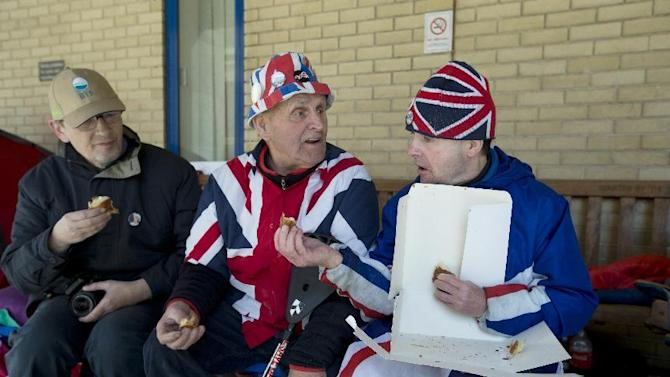 Royal fans John Loughrey, right and Terry Hutt, centre, share out the last of the royal pastries outside St Mary's Hospital, as they wait for Kate, Duchess of Cambridge, to arrive for the birth of her second child, in London, Tuesday, April, 28, 2015. The Duke and Duchess of Cambridge have offered a sweet surprise to die-hard fans, sending luxury pastries to thank them for camping outside the hospital and awaiting the birth of their second royal baby.(AP Photo/Alastair Grant)