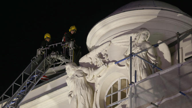 Firefighters inspect the roof of the Apollo Theatre after its ceiling partially collapsed during a performance in London, Thursday, Dec. 19, 2013. The ceiling of a London theatre partially collapsed Thursday night, showering a packed audience of about 700 with heaps of plaster, wood and dust, authorities and witnesses said. More than 80 people were injured, including at least seven seriously, and several trapped theater-goers had to be rescued. (AP Photo/Sang Tan)