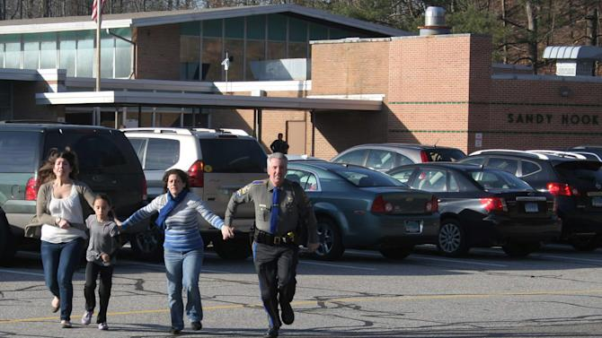FILE - In this Friday, Dec. 14, 2012, file photo provided by the Newtown Bee, a police officer leads two women and a child from Sandy Hook Elementary School in Newtown, Conn., where a gunman opened fire, killing 26 people, including 20 children. A prosecutor is planning to release a report on the investigation into the massacre at Sandy Hook Elementary School on Monday, Nov. 25, 2013, but the public will have to wait longer for the Connecticut state police's full accounting of the crime.(AP Photo/Newtown Bee, Shannon Hicks, File) MANDATORY CREDIT: NEWTOWN BEE, SHANNON HICKS