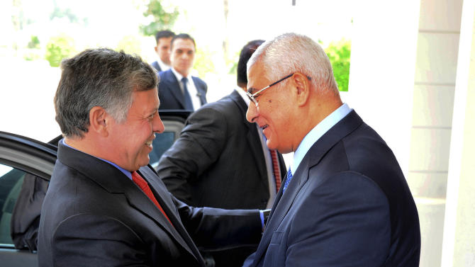 In this image released by the Egyptian Presidency, Egyptian President Adly Mansour, right, greets Jordan's King Abdullah II on his arrival to the presidential palace, Saturday, July 20, 2013. Jordan's King arrived in Egypt's capital on Saturday for a short visit -- the first visit by a head of state to Egypt since the ouster of President Mohamed Morsi on July 3, 2013. (AP Photo/Egyptian Presidency)