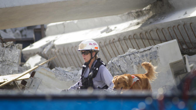 A Fire Rescue team member and her dog search for victims trapped in the collapsed parking garage at the Miami Dade College West campus in Doral, Fla. Tuesday, Oct. 10, 2012. One worker was killed and two others were trapped in the rubble. (AP Photo/J Pat Carter)