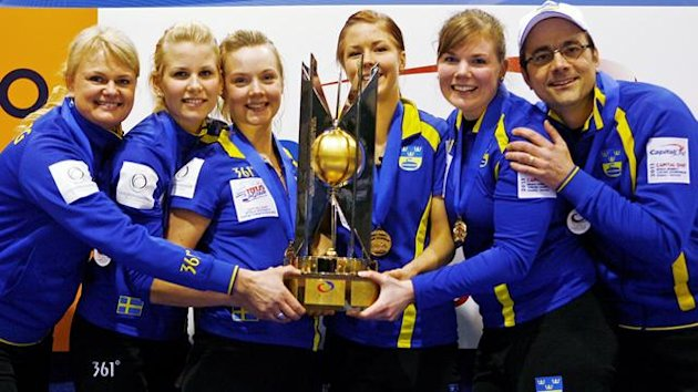 Sweden's skip Anette Norberg (L), third Cecilia Ostlund (2nd L), second Sara Carlsson (3rd L), lead Lotta Lennartsson (4th L), 5th player Karin Rudstrom (5th L) and coach Magnus Swartling hold the gold medal trophy after defeating Canada to win the World