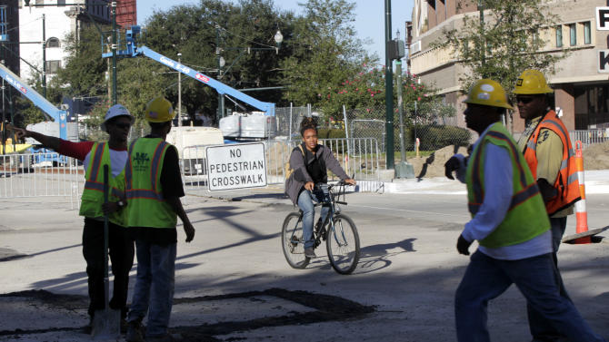 In this Nov. 8, 2012 photo, a woman passes by construction on street car tracks on Loyola Avenue in New Orleans. With the NFL football Super Bowl less than three months away, New Orleans is rushing to lay streetcar tracks through one of its busiest corridors to connect by trolley the Louisiana Superdome, where the big game will be played Feb. 3, and the French Quarter. At the same time, developers view the new streetcar as crucial in plans to spark a downtown renaissance where one of the city's most vibrant jazz districts has been replaced by parking lots and high rise buildings. (AP Photo/Gerald Herbert)