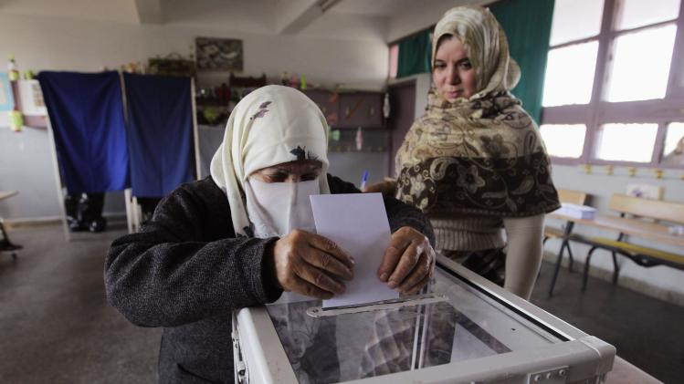 A woman casts ballot during presidential election in Algiers
