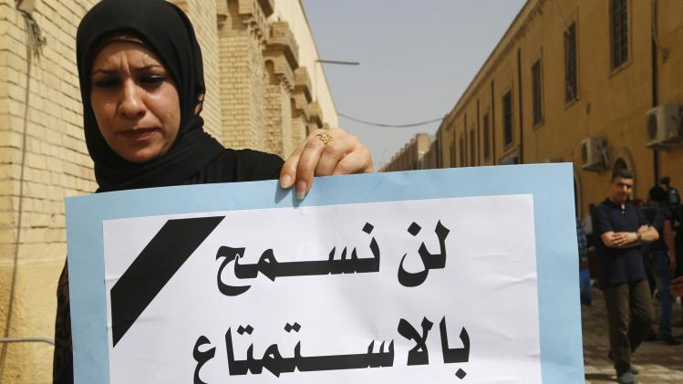 "An Iraqi woman holds a sign during a demonstration against the draft of the ""Al Ja'afari"" Personal Status Law in Baghdad"