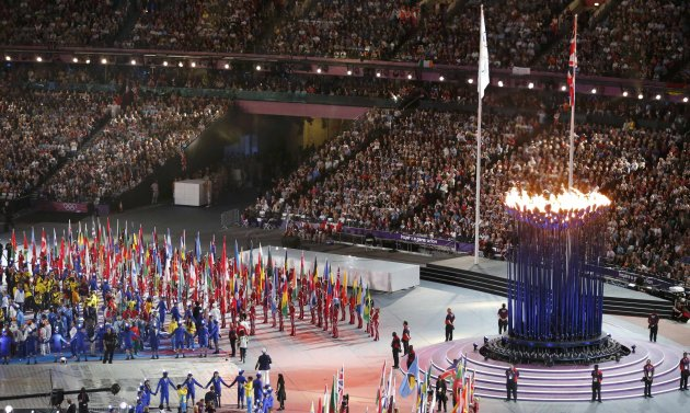 Athletes stand near the Olympic flame as they attend  the closing ceremony of the London 2012 Olympic Games at the Olympic Stadium