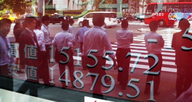"People are reflected on an electronic board of a securities firm in Tokyo, Thursday, May 16, 2013. The benchmark Nikkei 225 stock index rose to 15,139.56 early Thursday before falling back slightly on profit taking. It has gained about 75 percent since November in a rally linked to high hopes for Primer Minister Shinzo Abe's policies, which have been dubbed ""Abenomics."" Japan's economy enjoyed a stronger than expected recovery last quarter, growing at a 3.5 percent annual pace as the government stepped up public works spending and eased credit to encourage investment. (AP Photo/Koji Sasahara)"