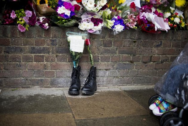 FILE - In this Friday, May 24, 2013 file photo, military boots are laid in tribute outside the Woolwich Barracks, in London, in response to the bloody attack on Wednesday when a British soldier was killed in the nearby street. Counterterrorism police on Saturday were questioning a friend of Michael Adebolajo, one of two suspects in the savage killing of British soldier Lee Rigby. The friend, Abu Nusaybah, was arrested immediately after he gave a television interview telling his story about how Adebolajo may have become radicalized. (AP Photo/Bogdan Maran, File)