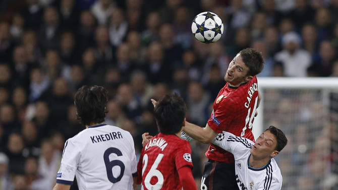 Manchester United's Michael Carrick, top right, is challenged by Real Madrid's Mesut Ozil from Germany, right, during the Champions League round of 16 first leg soccer match between Real Madrid and Manchester United at the Santiago Bernabeu stadium in Madrid, Wednesday Feb. 13, 2013. (AP Photo/Daniel Ochoa de Olza)