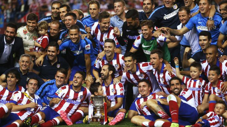 Atletico Madrid's team members celebrate with the trophy after they won the Spanish Super Cup against Real Madrid at the Vicente Calderon stadium in Madrid
