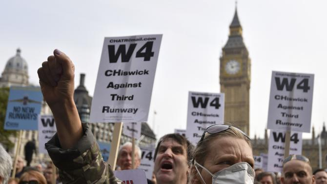 Anti Heathrow airport expansion protestors hold banners during a rally at Parliament Square in London