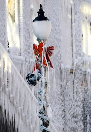 A street light is covered with icicles near a building which caught on fire in Plattsmouth, Neb., Friday, Jan. 3, 2014, and the water sprayed on it by fire fighters froze. Much of the American northeast and the midwest are suffering from sub-freezing temperatures. (AP Photo/Nati Harnik)