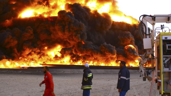 Firefighters try to put out a fire in an oil tank in Es Sider port