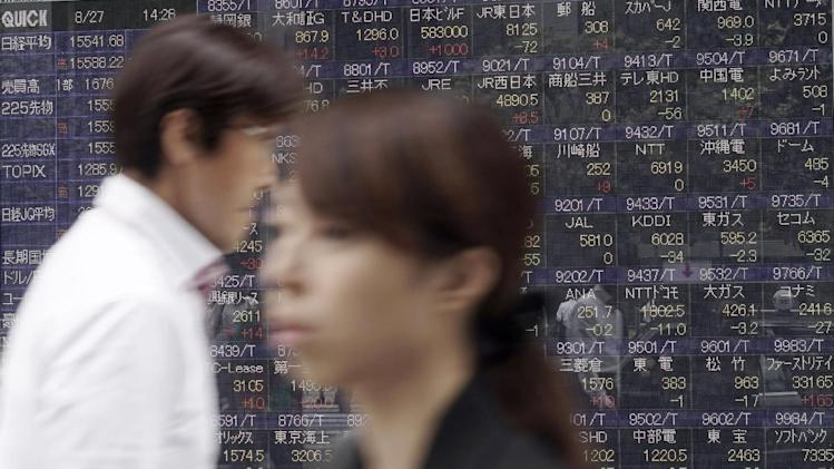 People walk past an electronic stock board of a securities firm in Tokyo, Wednesday, Aug. 27, 2014. Asian stock markets were mostly higher Wednesday after the latest record close for the Standard & Poor's 500, though gains were modest and Japan and Hong Kong lost ground after early advances. (AP Photo/Eugene Hoshiko)