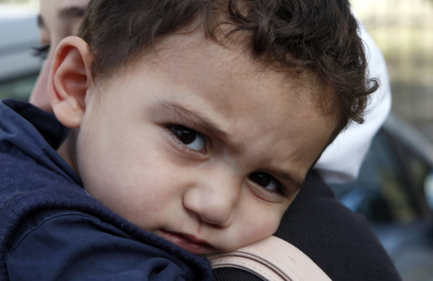 "Bushr Al Tawashi looks at the photographer as he is carried by his mother Arin Al Dakkar, outside of a private Sigma TV station, in Nicosia, Cyprus, Friday, Oct. 26, 2012. Bushr Al Tawashi, a 2-year-old Syrian boy who was believed dead after his family inadvertently left him behind as they fled shelling in Damascus last summer has been reunited with his parents in Cyprus, a lawyer said. ""You can imagine how they felt when they were told their son was alive after bearing all this guilt thinking that he was dead,"" lawyer Stella Constantinou told The Associated Press. (AP Photo/Petros Karadjias)"