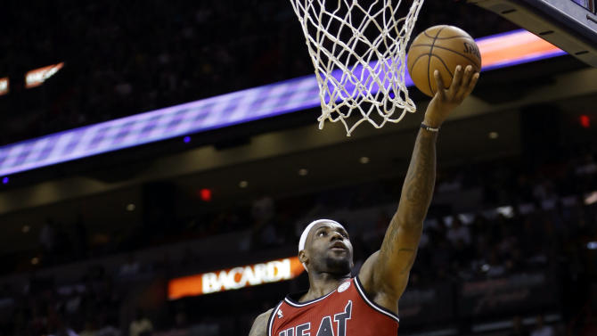 Miami Heat's LeBron James (6) goes to the basket against Portland Trail Blazers' Damian Lillard, left, during the first half of an NBA basketball game in Miami, Tuesday, Feb. 12, 2013. James became the first player in NBA history to score 30 points and shoot at least 60 percent in six straight games as the Heat won 117-104. (AP Photo/Alan Diaz)