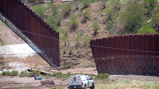 A border patrol vehicle stands guard at a section of collapsed fence just west of the Mariposa Port of Entry in Nogales, Ariz., Sunday, July 27, 2014, after severe storms in southern Arizona over the weekend knocked down a chunk of the metal border fence that divides Mexico and the U.S. Rain runoff from the storms destroyed about 60 feet worth of fence and caused damage to homes just north of it. (AP Photo/Nogales International, Jonathan Clark)