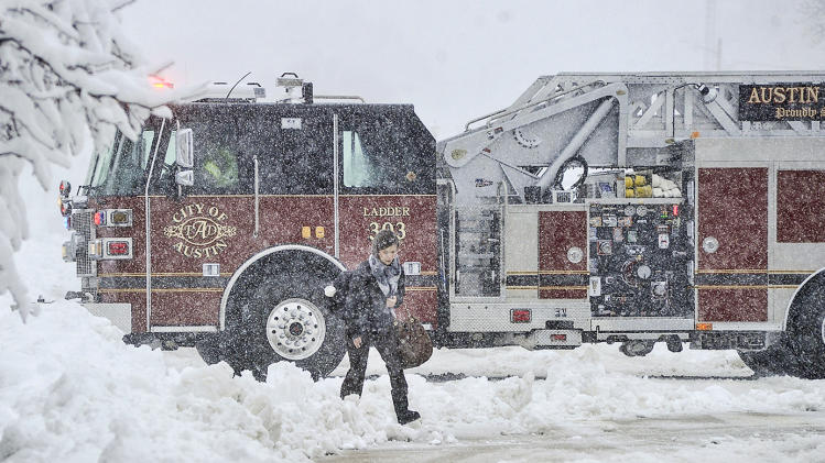 Kirsten Cole walks to work as an Austin fire truck returns to base from a call Thursday morning, May 2, 2013 in Austin, Minn. as heavy snow continues to fall on the area. Winter made a return appearance in southeastern Minnesota where residents are digging out of more than a foot of new snow.  (AP Photo/Austin Daily Herald, Eric Johnson)